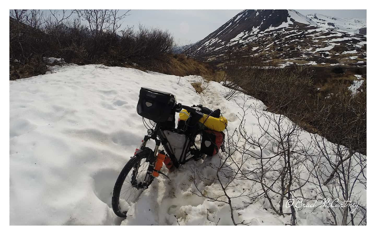 Carrying my bike through the late season Snow drifts of Alaska's Devils Pass