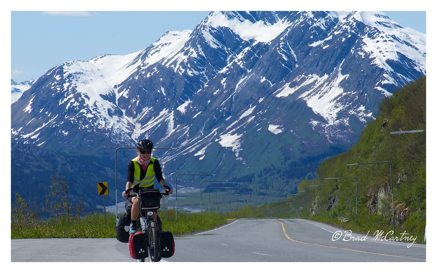 Lucile cycling Richardson Highway about half way to the top of Thompson Pass near Valdez